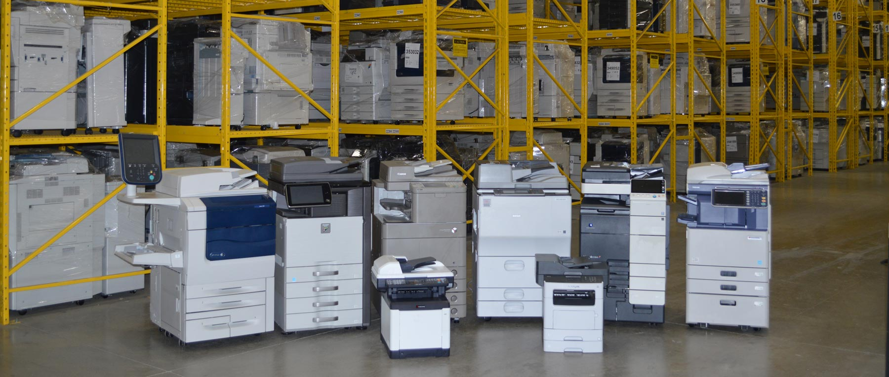 6 large and 2 small copiers ranged in front of warehouse shelves of copiers
