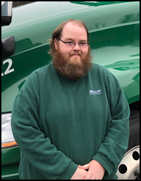 Chris, Freight Coordinator in front of Wullf Enterprises green tractor-trailer.