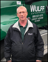 Freight Coordinator Ray in front of green Wulff Enterprises tractor-trailer.