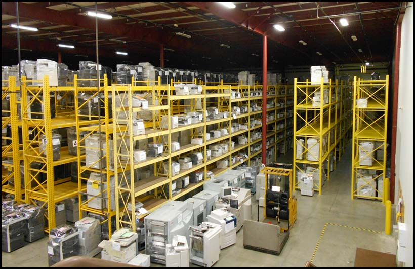 Long view of warehouse with rows of high shelving filled with office equipment